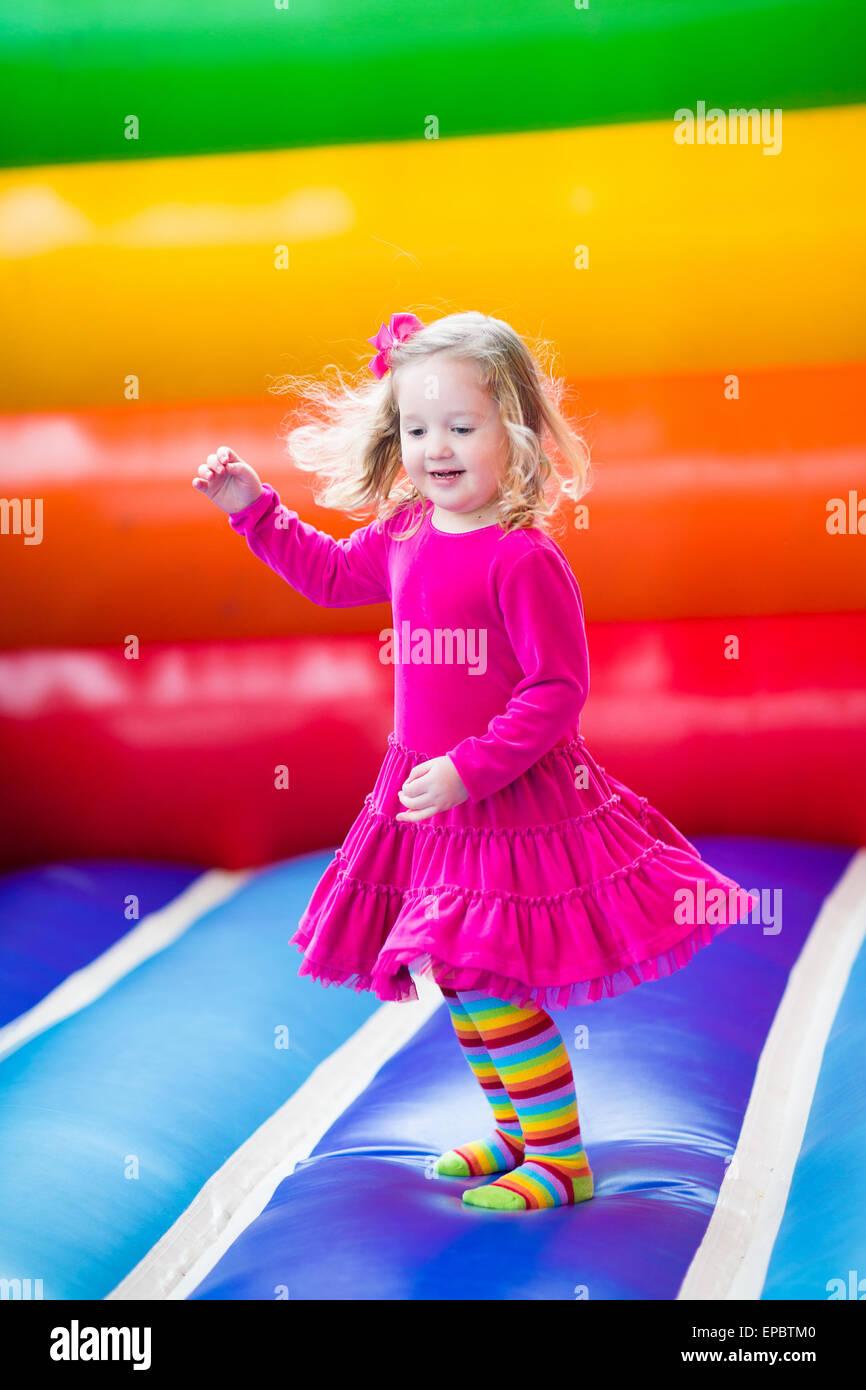 Niedliche lustige Vorschule kleine Mädchen spielen, springen und hüpfen in einer Hüpfburg auf Geburtstagsparty Stockbild