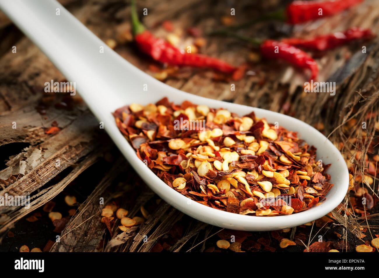 Zerkleinerten Chili Gewürz in einem weißen Löffel auf Holz Stockbild