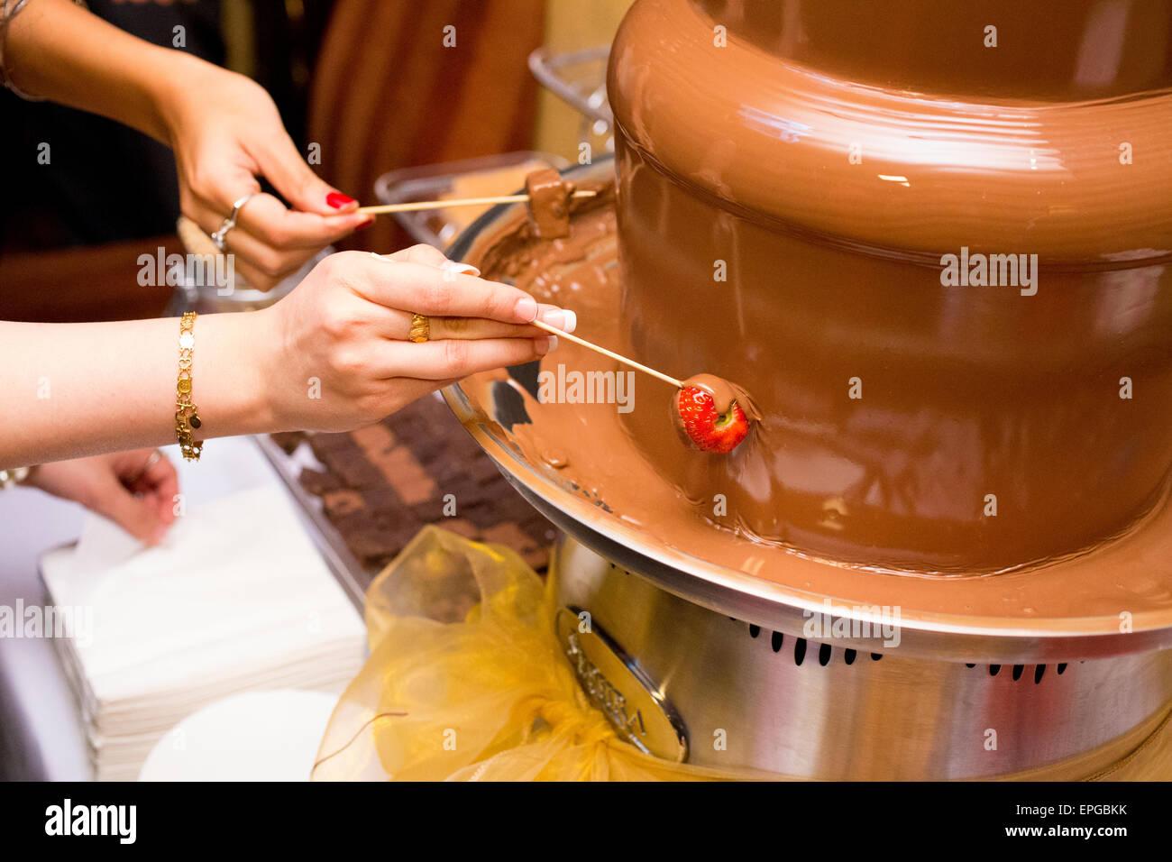 Hände eintauchen Snacks in einem Schokoladenbrunnen Stockbild