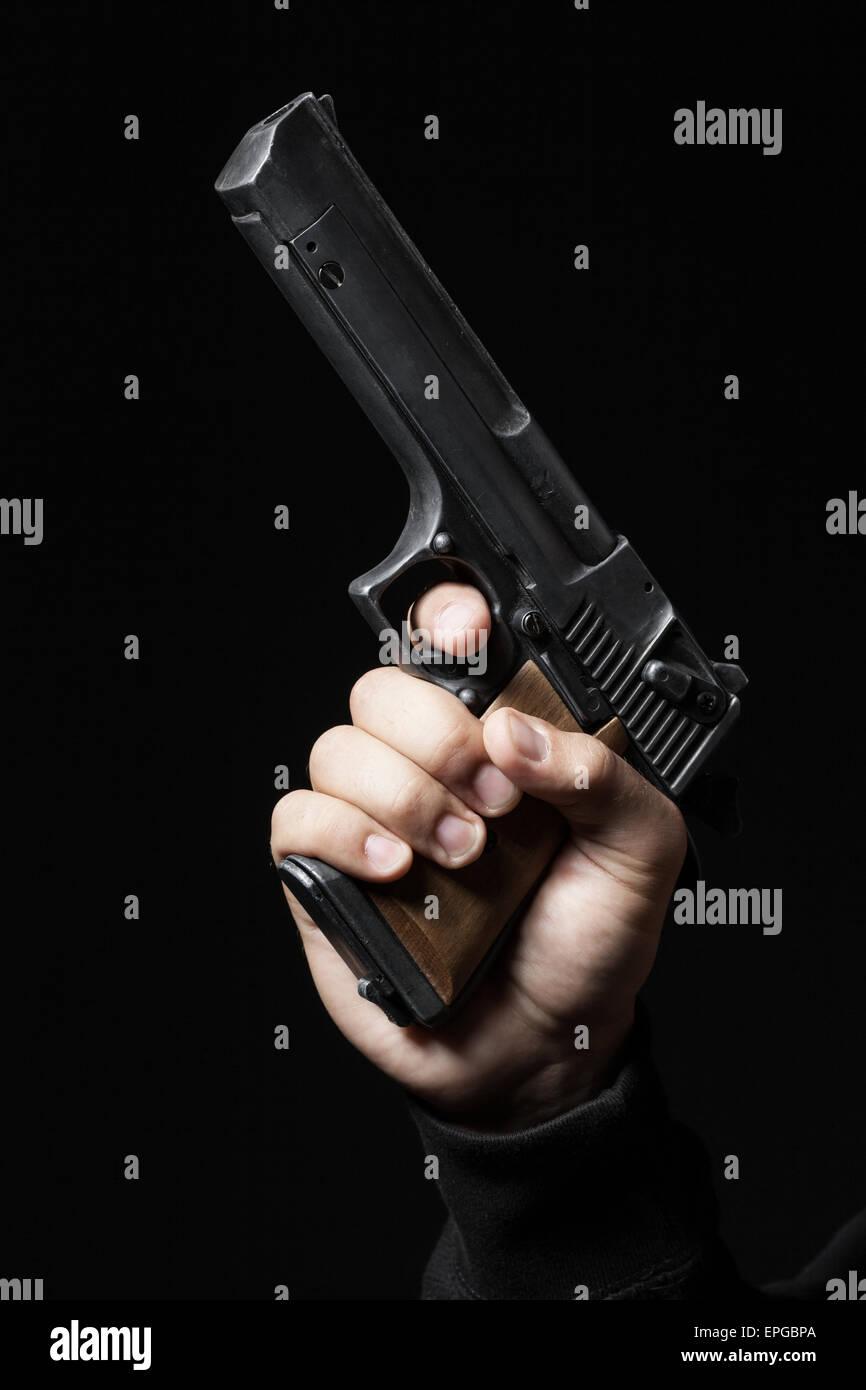 männliche Hand mit Gewehr auf schwarzem Hintergrund isoliert Stockbild