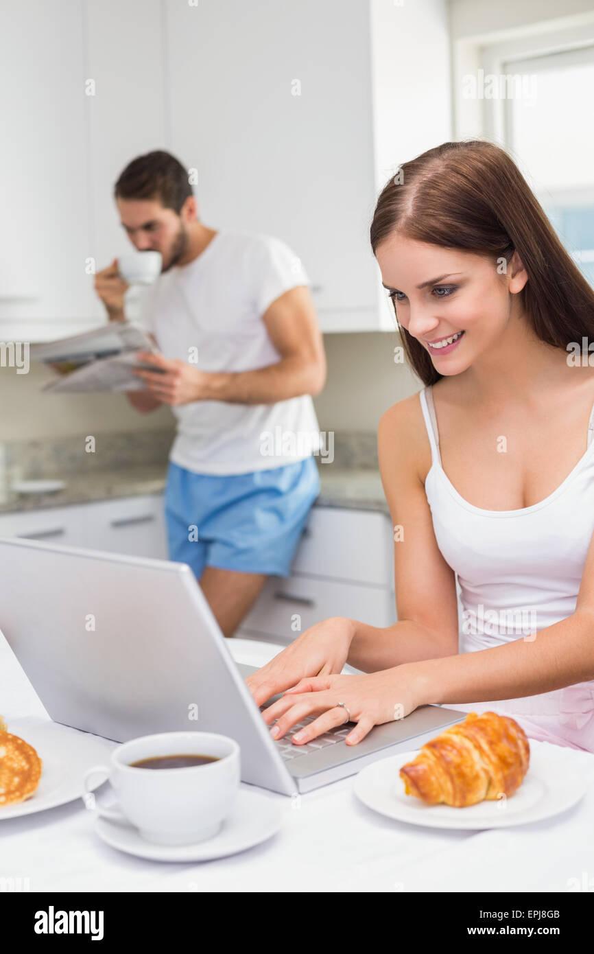 Junge Frau mit Laptop beim Frühstück Stockbild