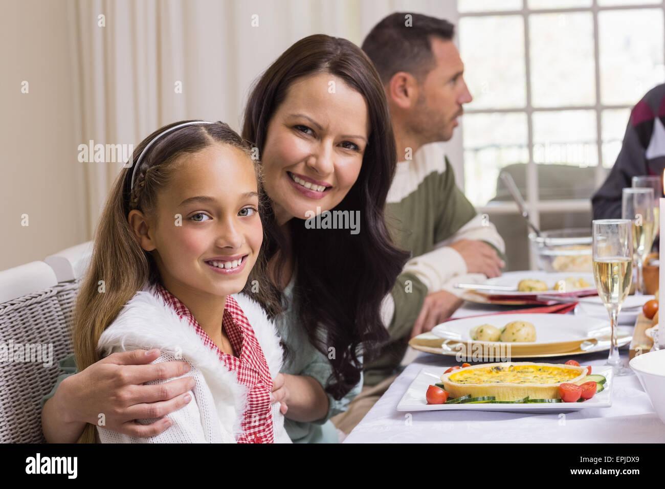 Mädchen und Mutter am Weihnachtsessen lächelnd in die Kamera Stockbild