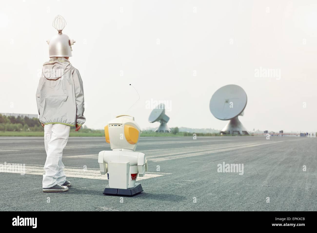 Junge verkleidet als Raumfahrer mit Roboter Stockbild