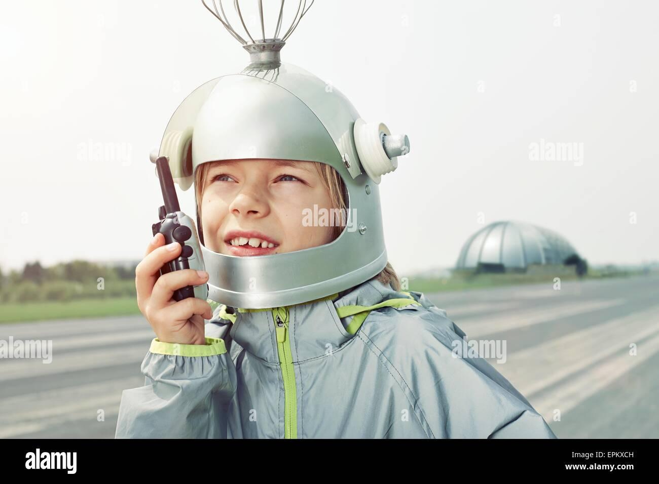 Junge verkleidet als Raumfahrer hält walkie-talkie Stockbild
