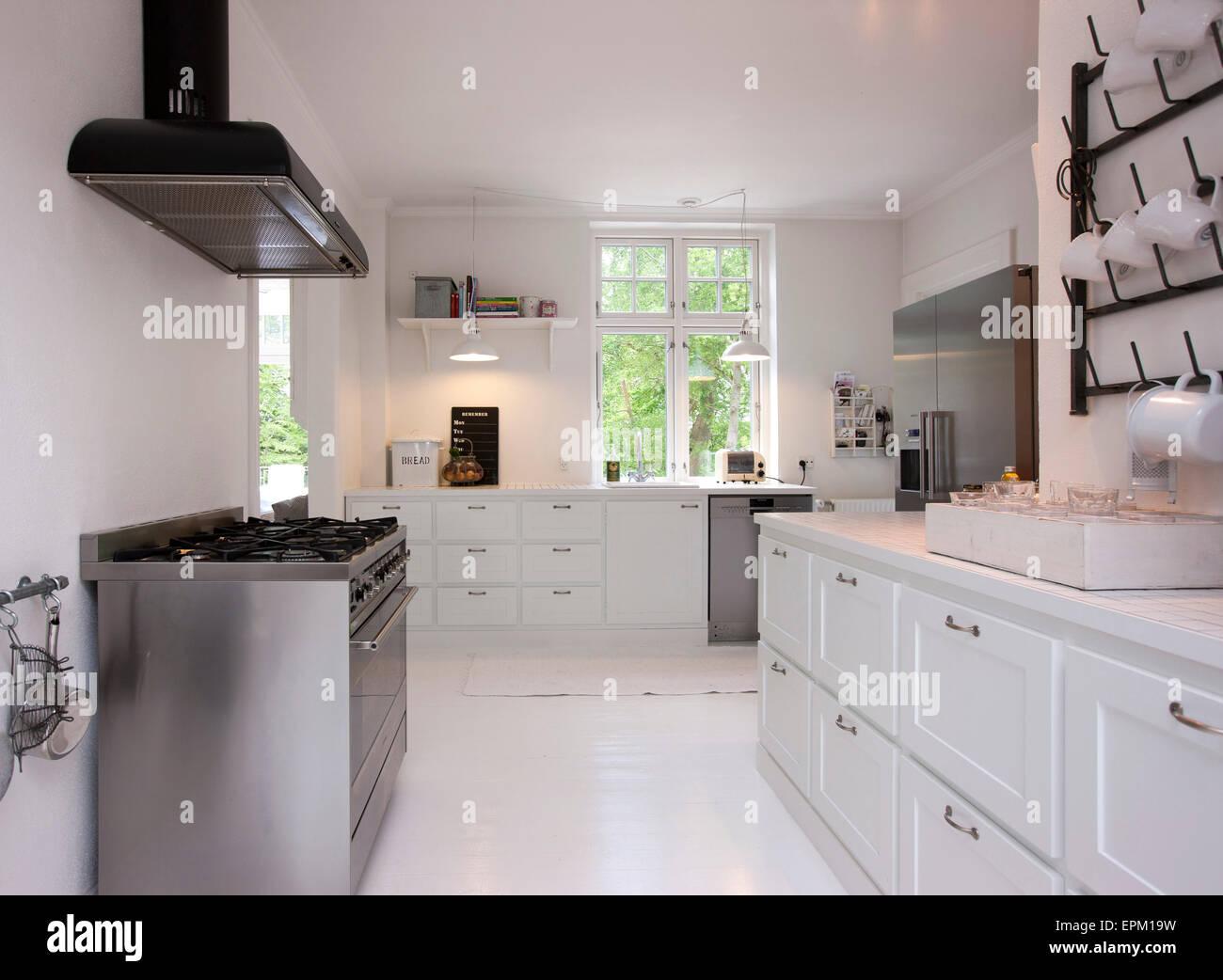 Weiße Küche mit Edelstahl-Herd im Renovierungs Hanne Davidsen, Silkesborg, Dänemark. Stockbild