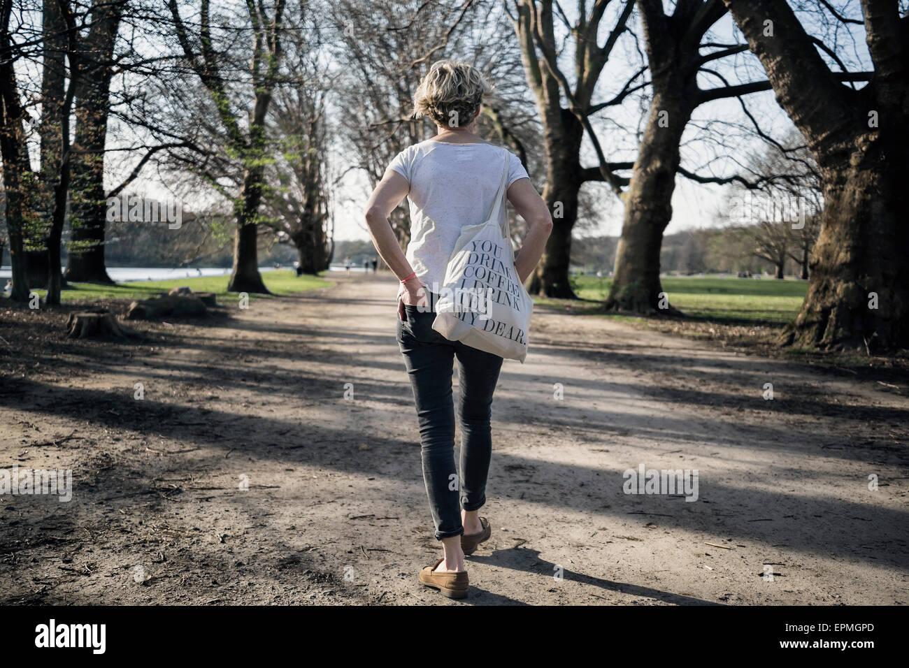 Deutschland, Köln, single-Frau zu Fuß am Stadtpark Stockbild