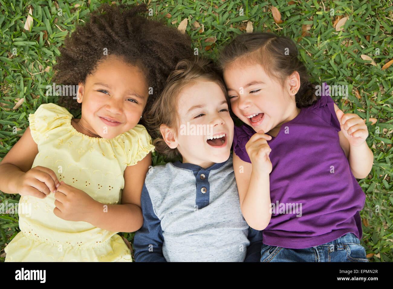 Drei Kinder auf dem Rücken im Gras liegend, nachschlagen und lachen. Stockbild