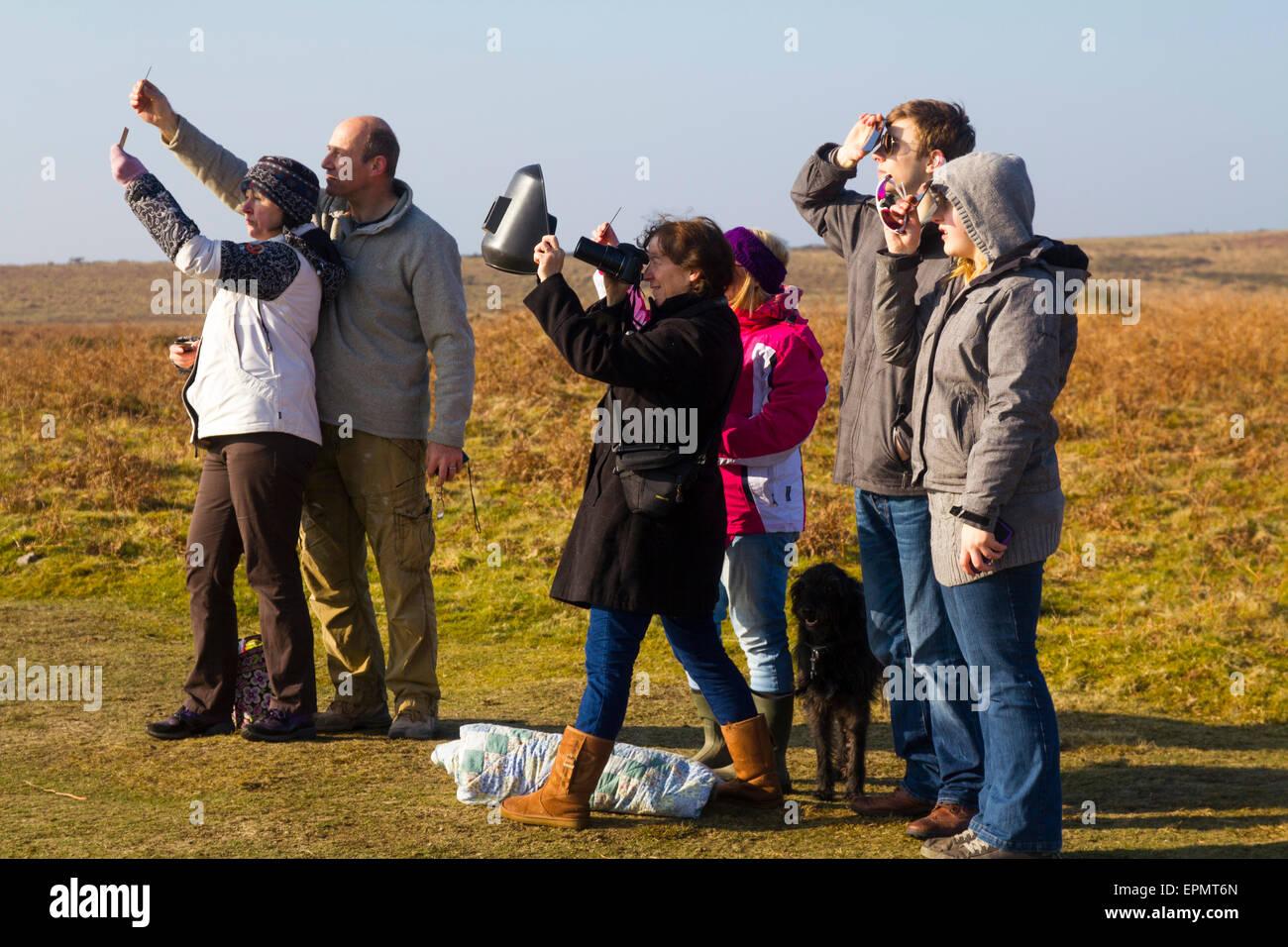 Leute beobachten die sensationelle partielle Sonnenfinsternis, 20. März 2015, am Moor, Halbinsel Gower, Wales, Stockbild