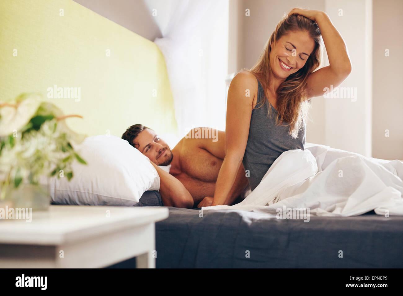 Glückliches junges Paar morgens am Bett aufwachen. Junger Mann und Frau lächelnd, entspanntes Gefühl Stockbild