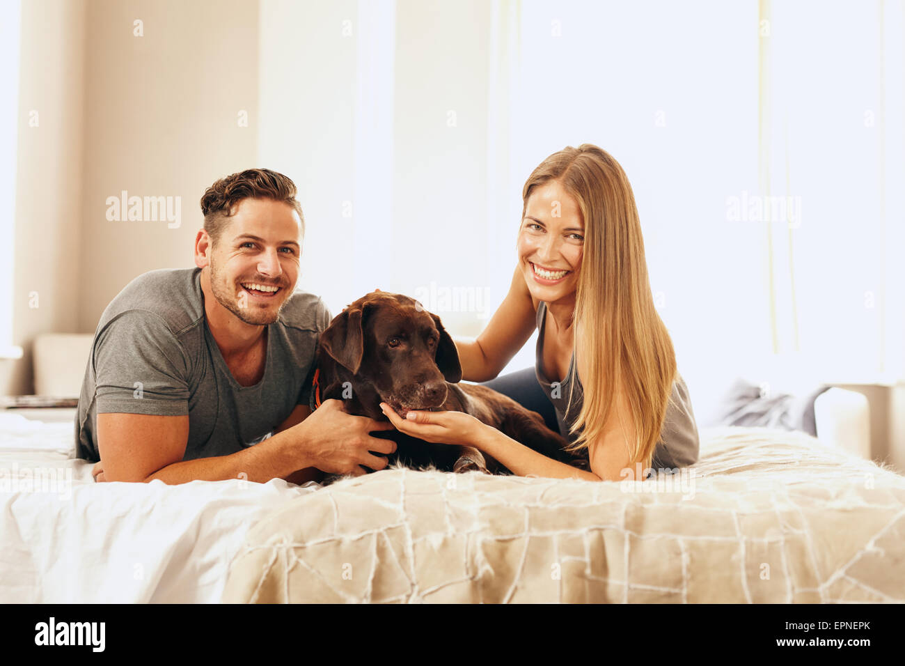 Aufnahme eines jungen Paares auf dem Bett liegend mit ihrem Hund. Fröhlicher Mensch und Frau Blick in die Kamera Stockbild