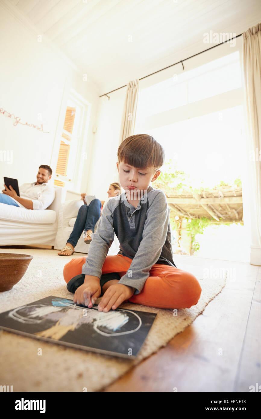 Kleine Schüler sitzen auf Bodenzeichnung mit seinen Eltern im Hintergrund auf Couch sitzen. Familie im Wohnzimmer. Stockbild