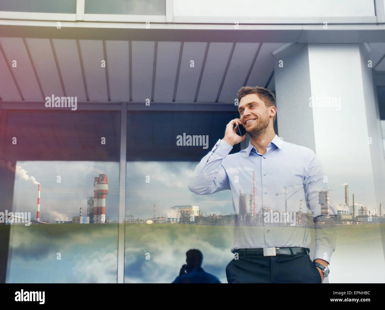 Doppelbelichtung Geschäftsmann mit Phone-Gerät und Industrieunternehmen auf städtebauliche Hintergrund Stockbild