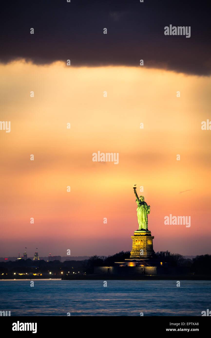Freiheitsstatue unter einer dramatischen Sonnenuntergang Licht aus Brooklyn, New York aus gesehen Stockbild