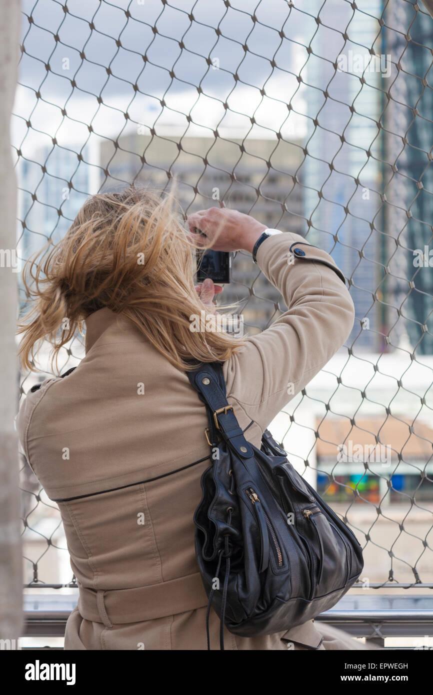 Frau, die Fotos von der Aussicht von der Spitze des Denkmals für den großen Brand von London Stockbild