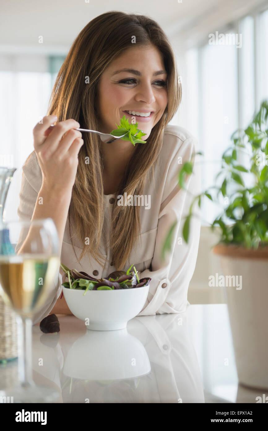 Junge Frau essen Salat im Wohnzimmer Stockbild
