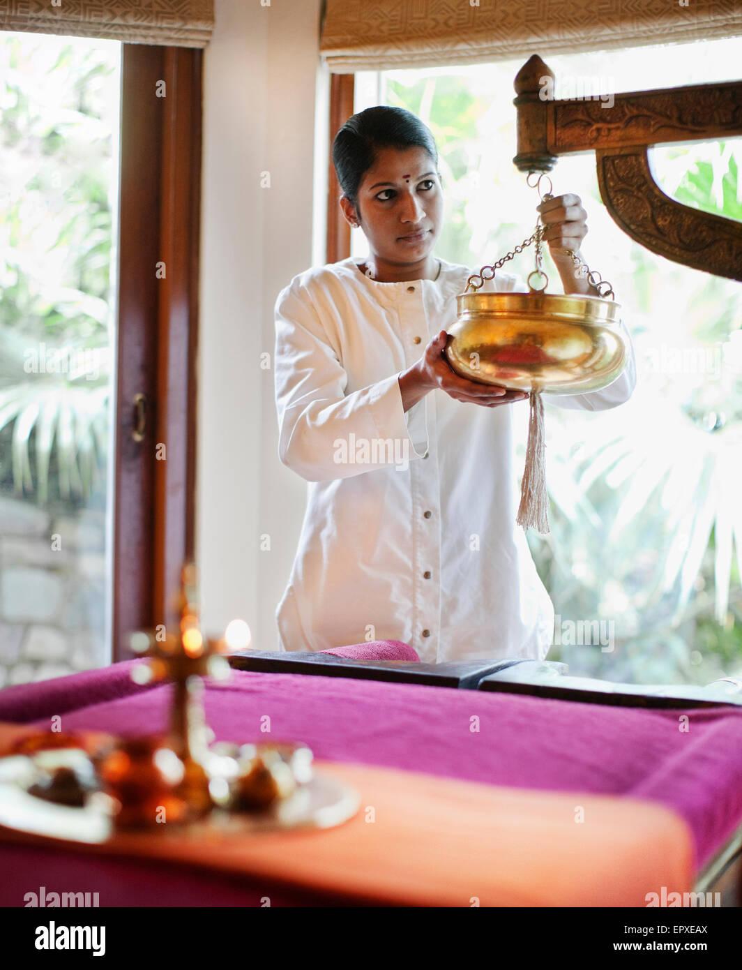 Ein Spa-Therapeuten bereitet das Sariva Zimmer für ein Shirodhara Ayurveda-Behandlung im Ananda Spa, Ananda Stockbild