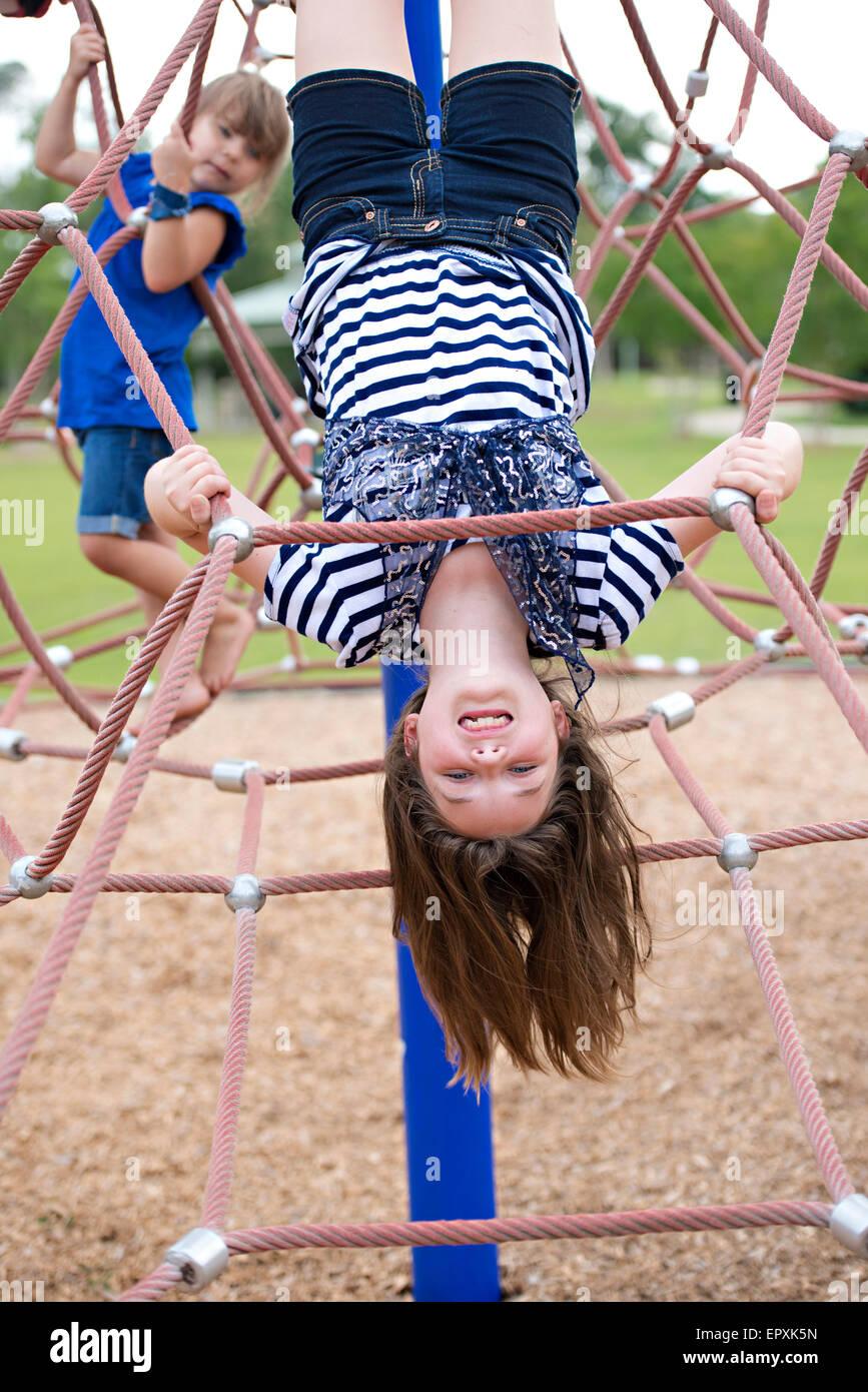 Mädchen hängt kopfüber am Seil Klettergerüst auf Outdoor-Park ...