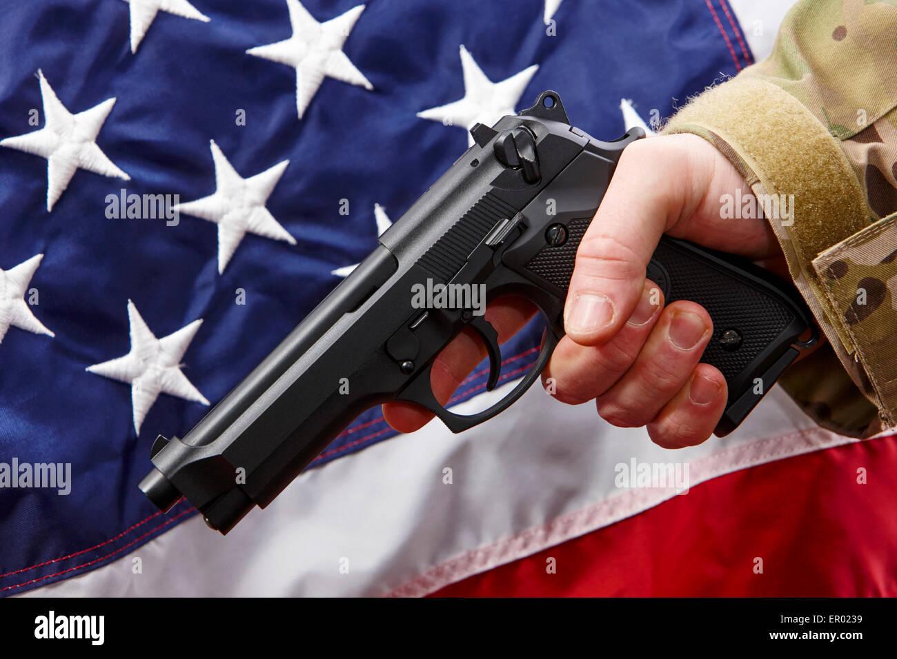Mann in Strapazen holding Beretta Pistole vor Vereinigte Staaten von Amerika Flagge Stockbild