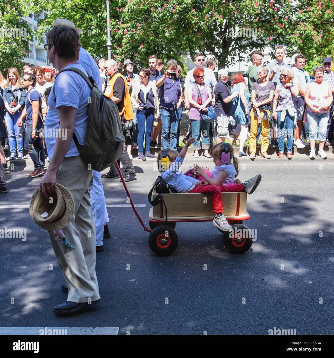 Kreuzberg, Berlin, Deutschland, 24. Mai 2015. Zwei kleine Kinder mit Ohrenschützer in Holz Wagen in die Parade Stockbild