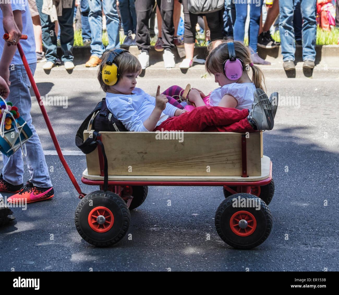Kreuzberg, Berlin, Deutschland, 24. Mai 2015. Zwei kleine Kinder mit Ohrenschützer in Holz Wagen in die Parade als Stockfoto