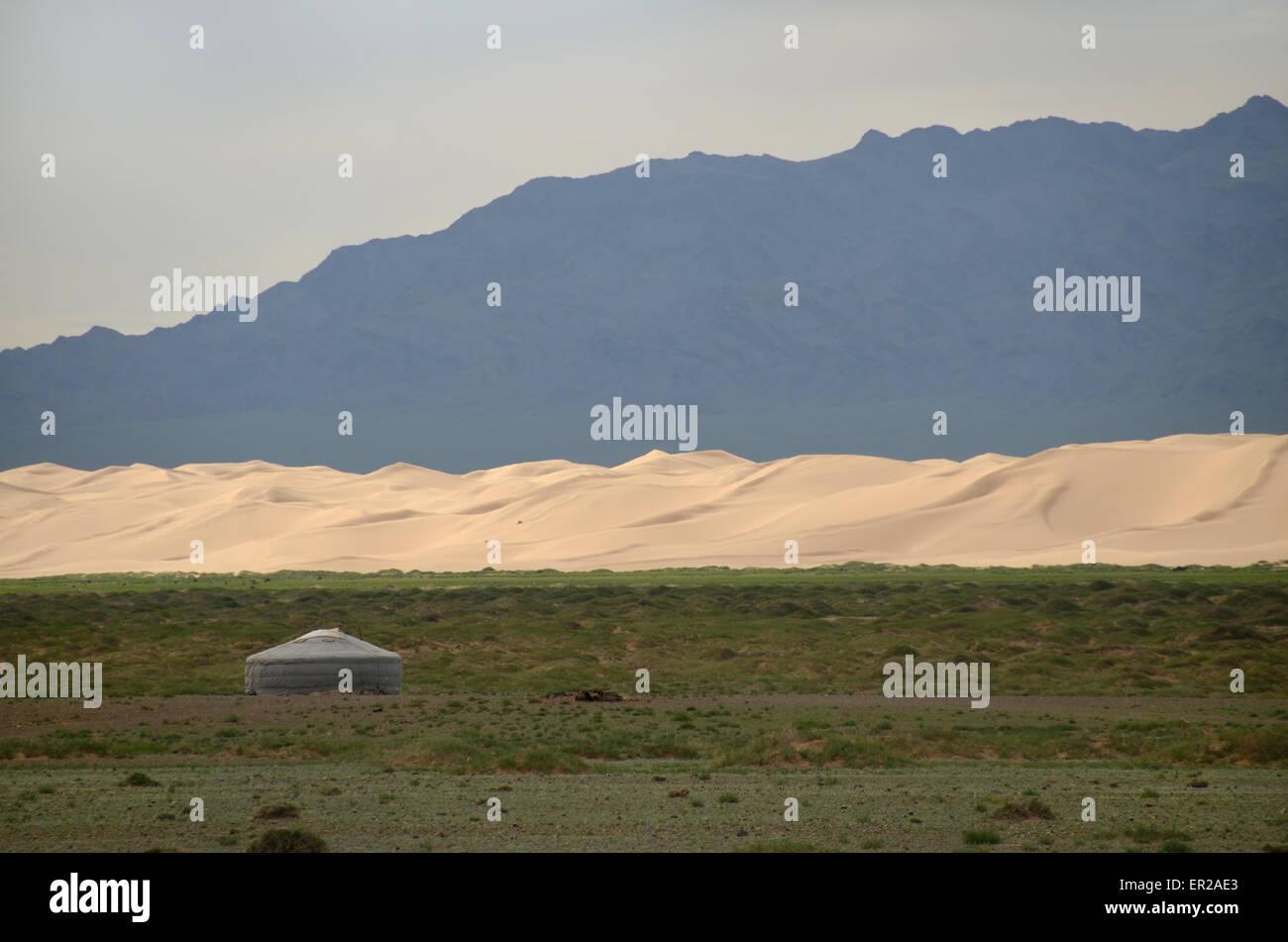 Eine Jurte in der Gobi-Wüste vor Sanddünen und Gebirge, Omnogovi Provinz, Mongolei Stockfoto