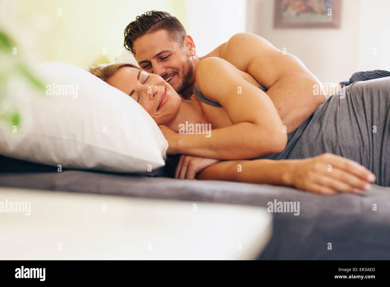 Junges Paar auf Bett liegend zusammen im Schlafzimmer verliebt. Glücklicher Mann und Frau morgens aufwachen. Stockbild