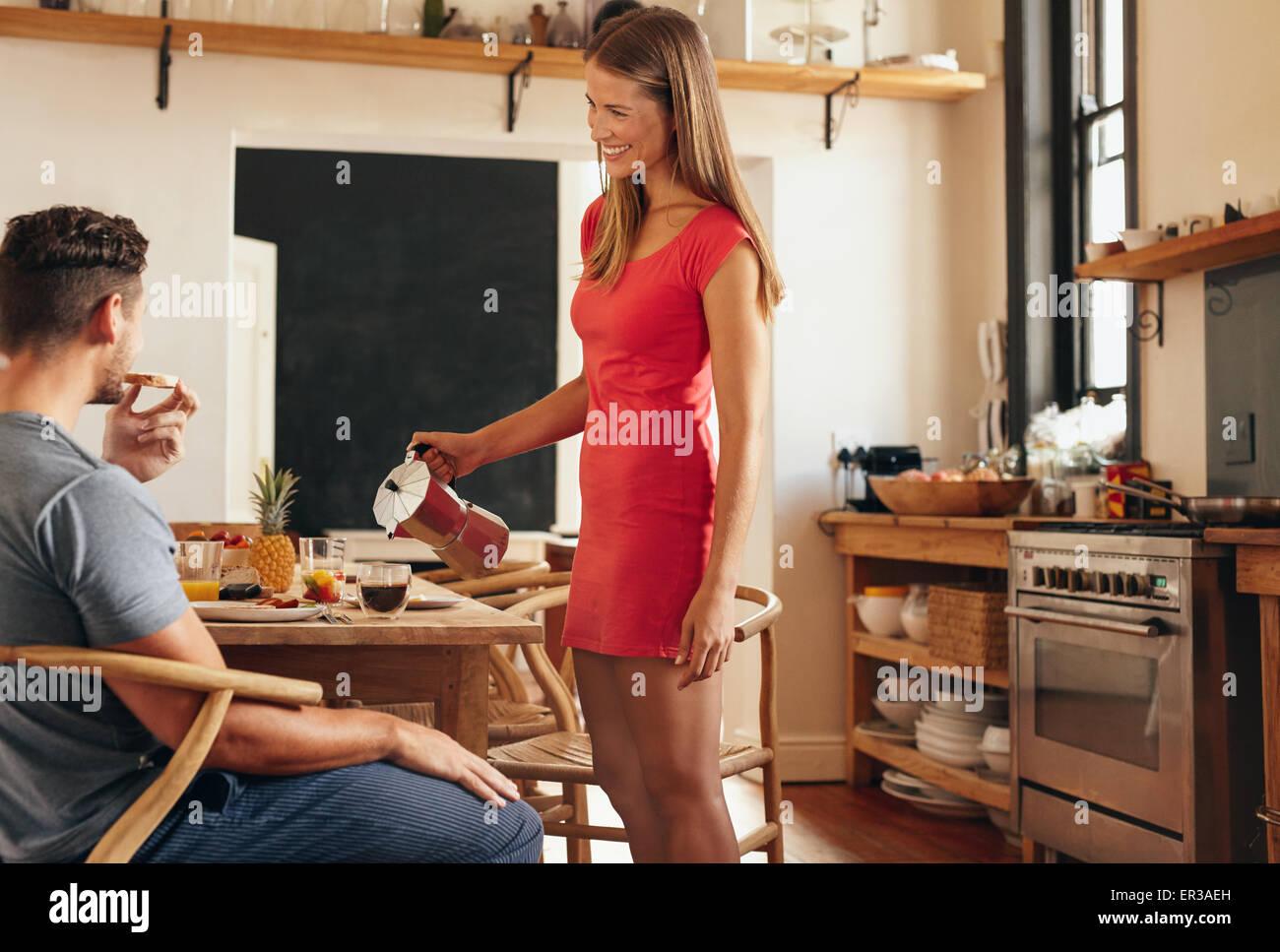 Innenaufnahme des Paares mit Frühstück im heimischen Küche. Junge Frau stehen und servieren von Kaffee Stockbild