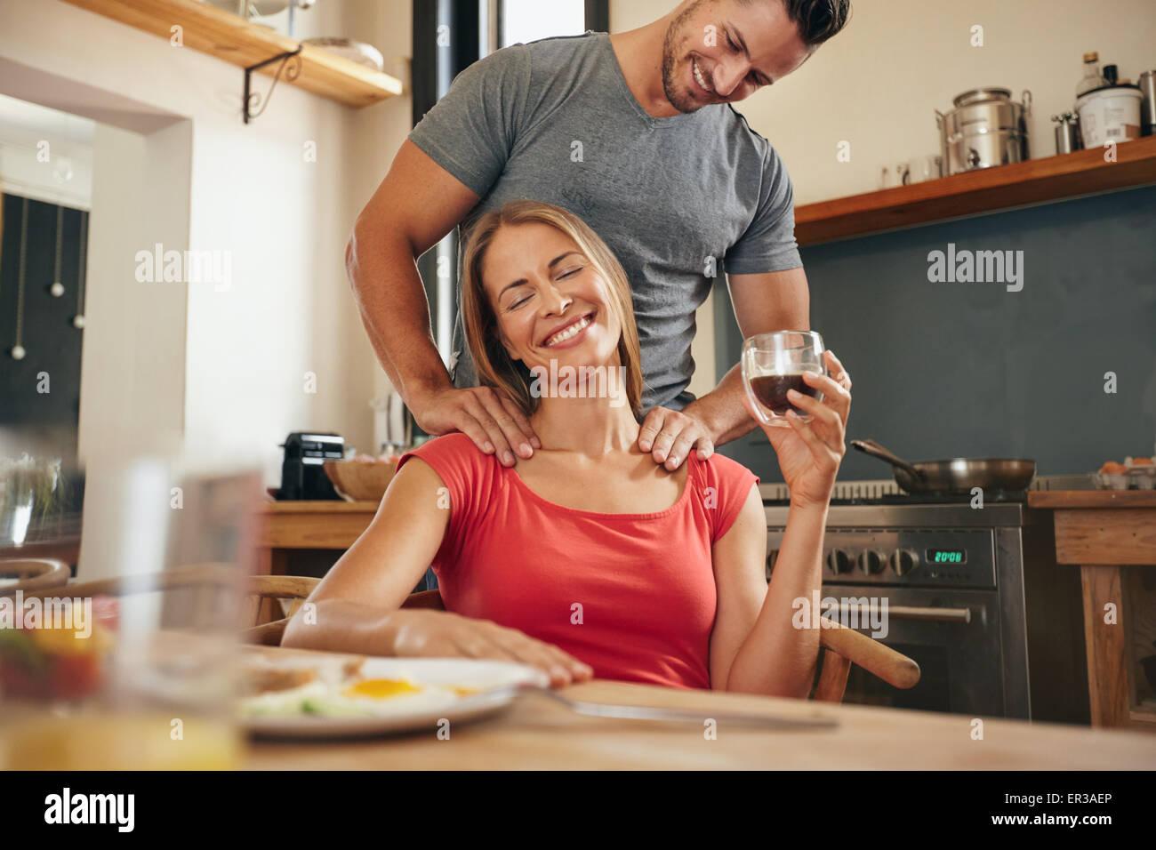 Glückliche junge Frau sitzt am Frühstück Tablet halten Tasse Kaffee immer eine Schultermassage von Stockbild