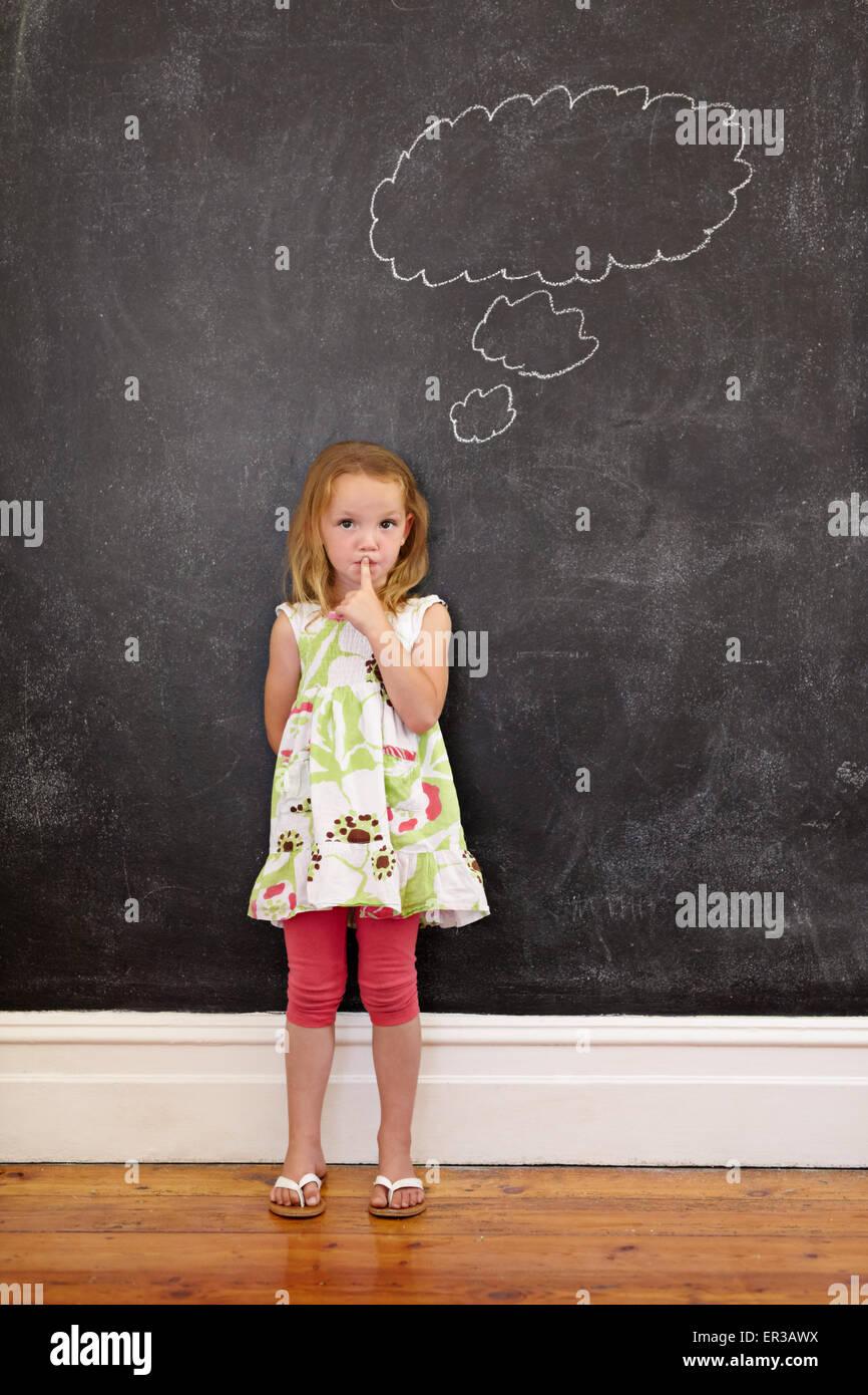 Niedliche kleine Mädchen mit dem Finger auf die Lippen und eine Gedankenblase auf Tafel. Kleines Mädchen Stockbild