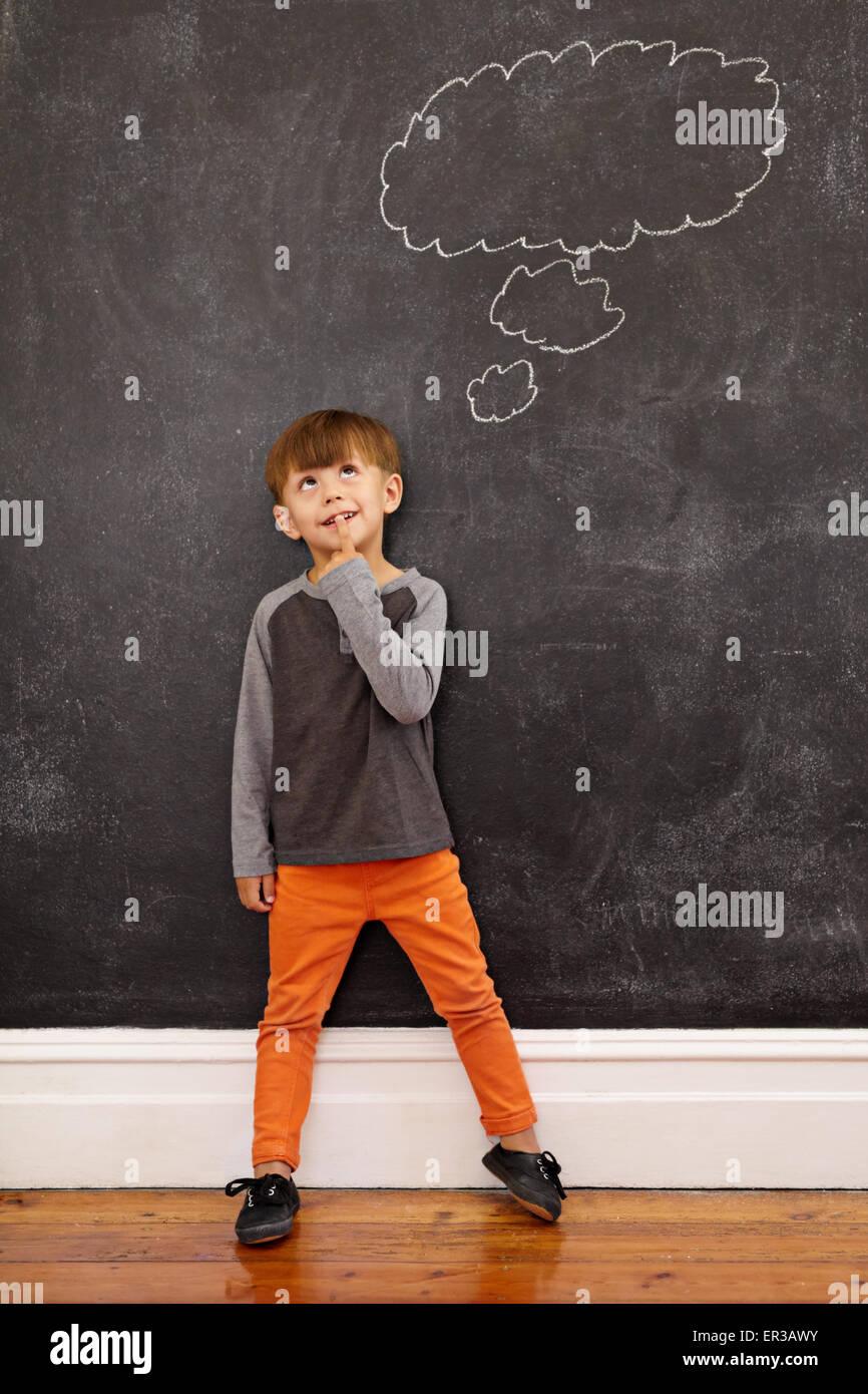 Kind mit einer Sprechblase auf der Tafel zu denken. Voller Länge Schuss von niedlichen kleinen Jungen zu Hause Stockbild