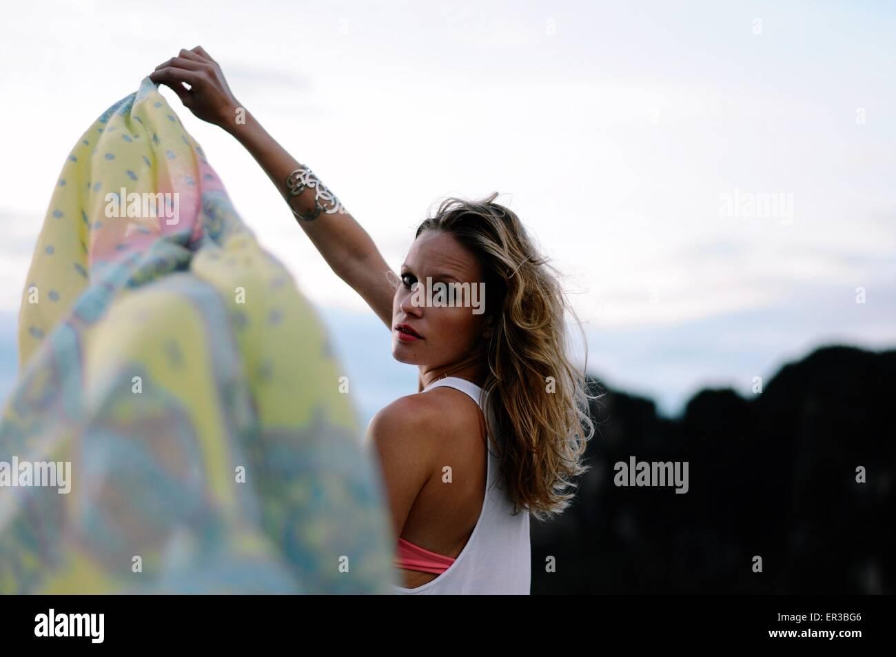 Frau hält einen Sarong im Wind am Strand Stockbild