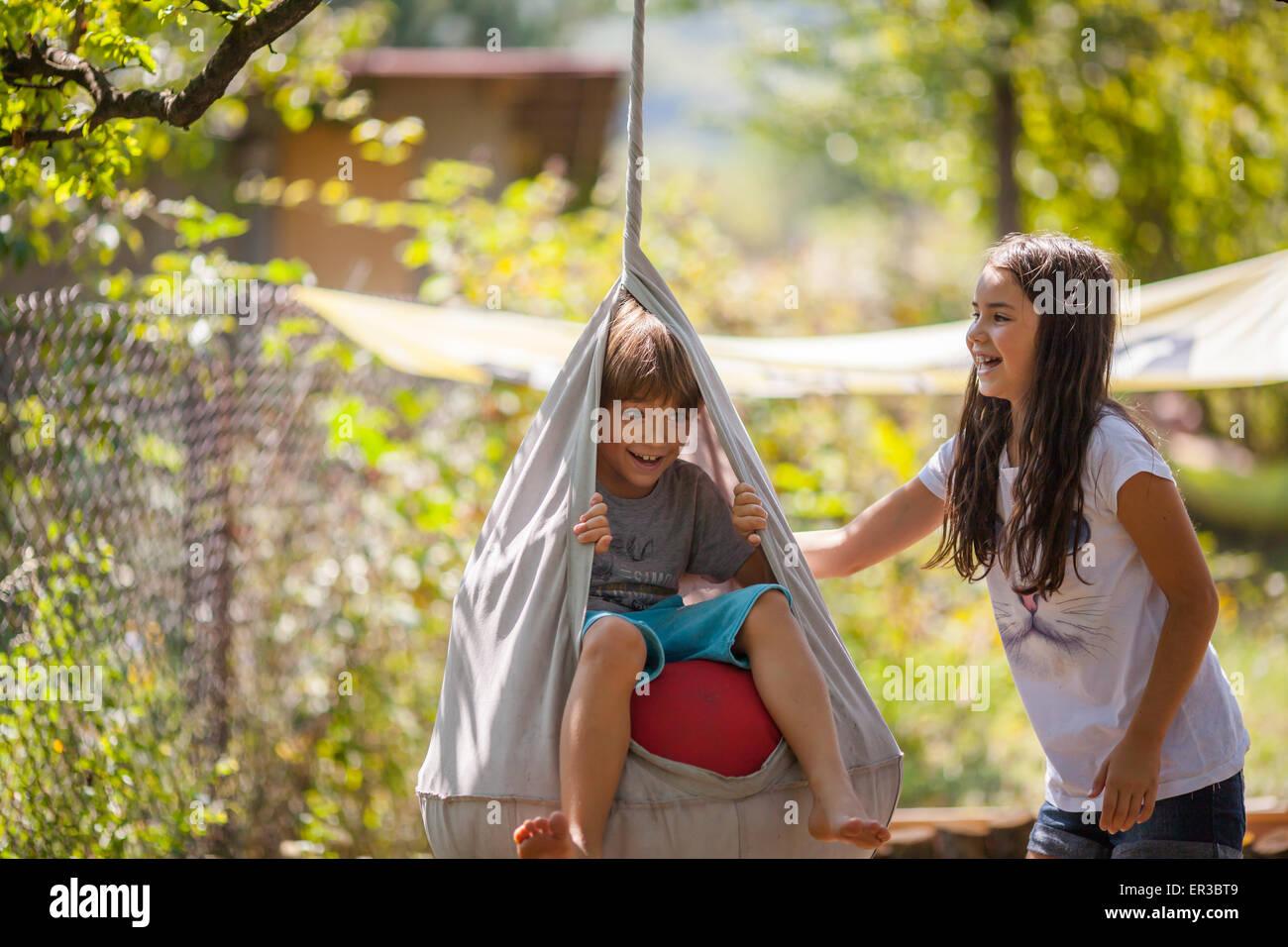 Jungen und Mädchen spielen auf einer Schaukel im Garten Stockbild
