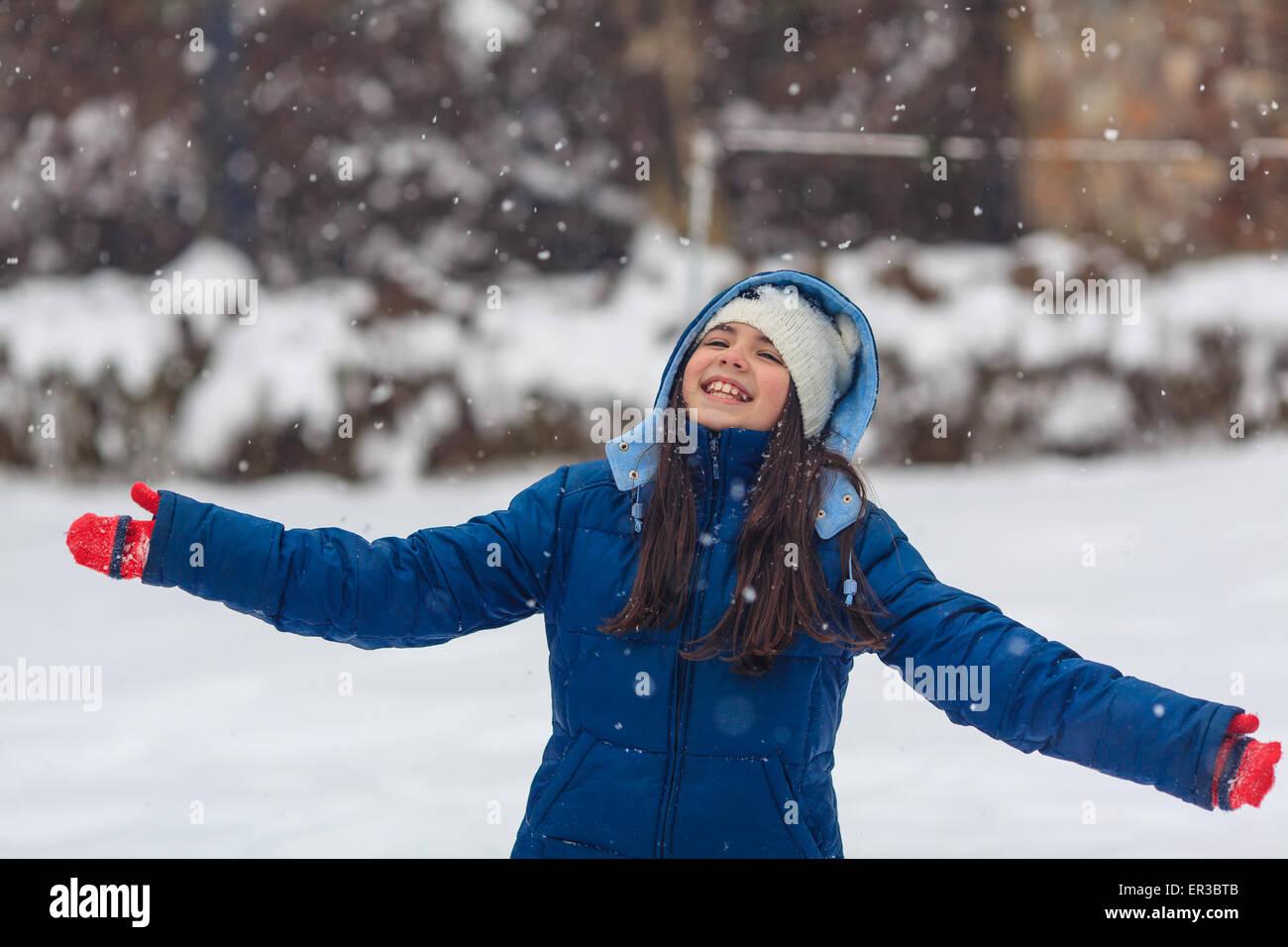 Mädchen mit ausgestreckten Armen spielen im Schnee Stockbild