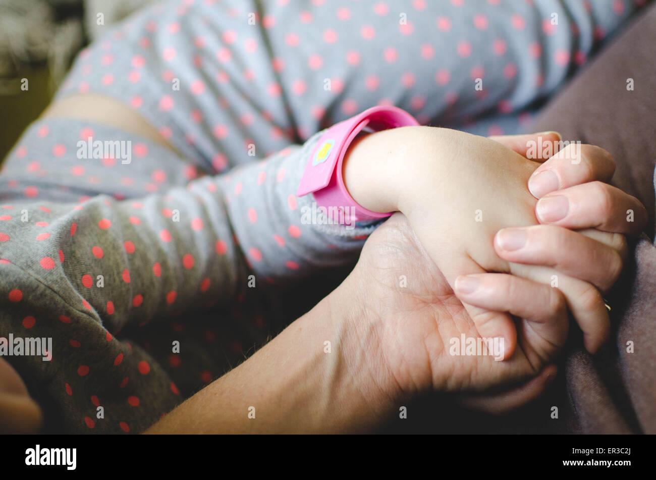 Mutter und Tochter beisammen sitzen und Hand in Hand Stockbild