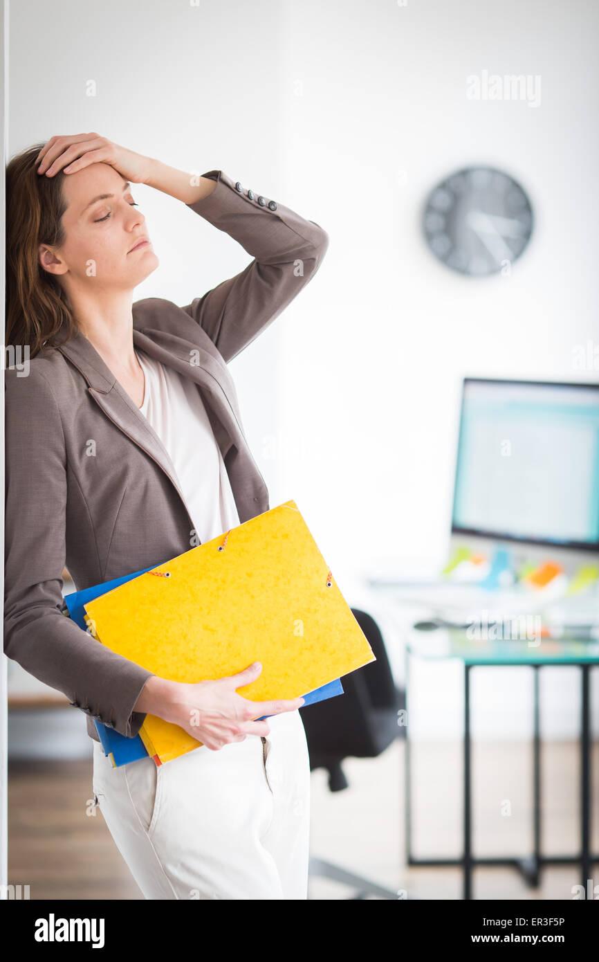 Frau bei der Arbeit, die unter Kopfschmerzen leiden. Stockbild