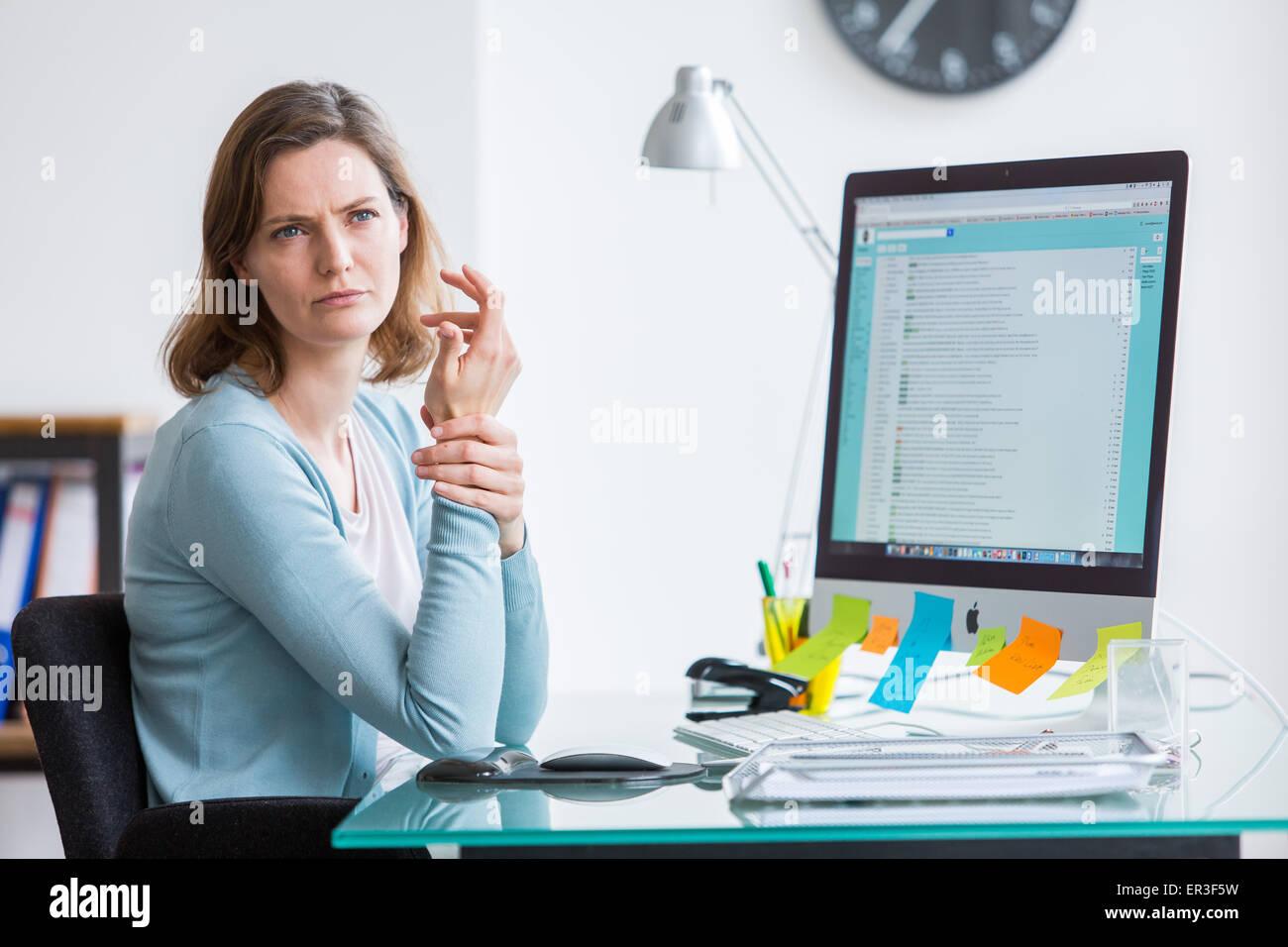 Frau bei der Arbeit leiden, Schmerzen am Handgelenk. Stockbild