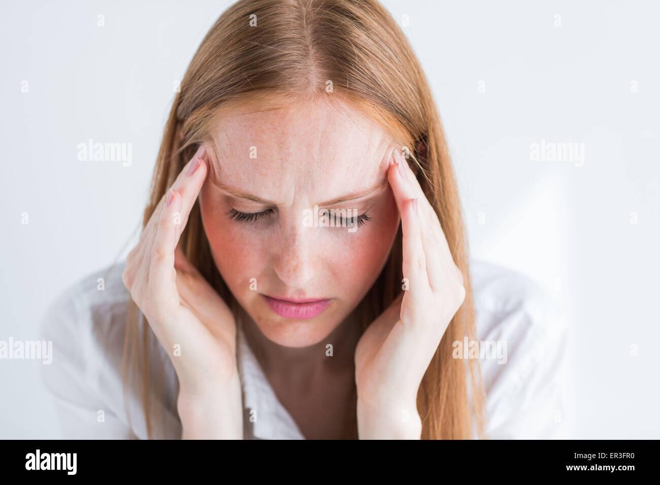 Frau, die unter Kopfschmerzen leiden. Stockbild