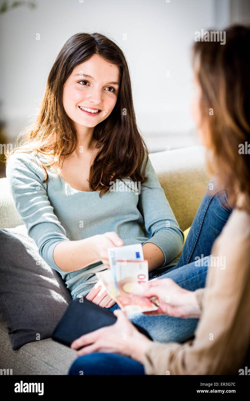 Mutter gibt ihrer Tochter Taschengeld. Stockbild