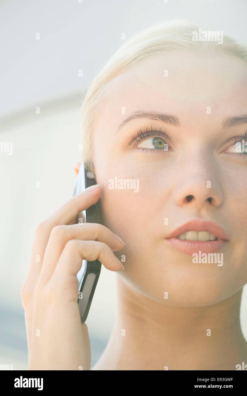 Frau am Handy mit ernsten Gesichtsausdruck Stockbild