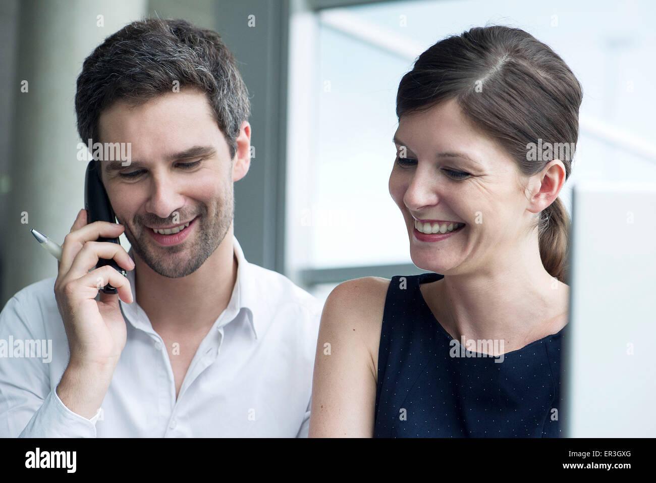 Kollegen zusammen, lächelnd Mann reden über Handy Stockbild