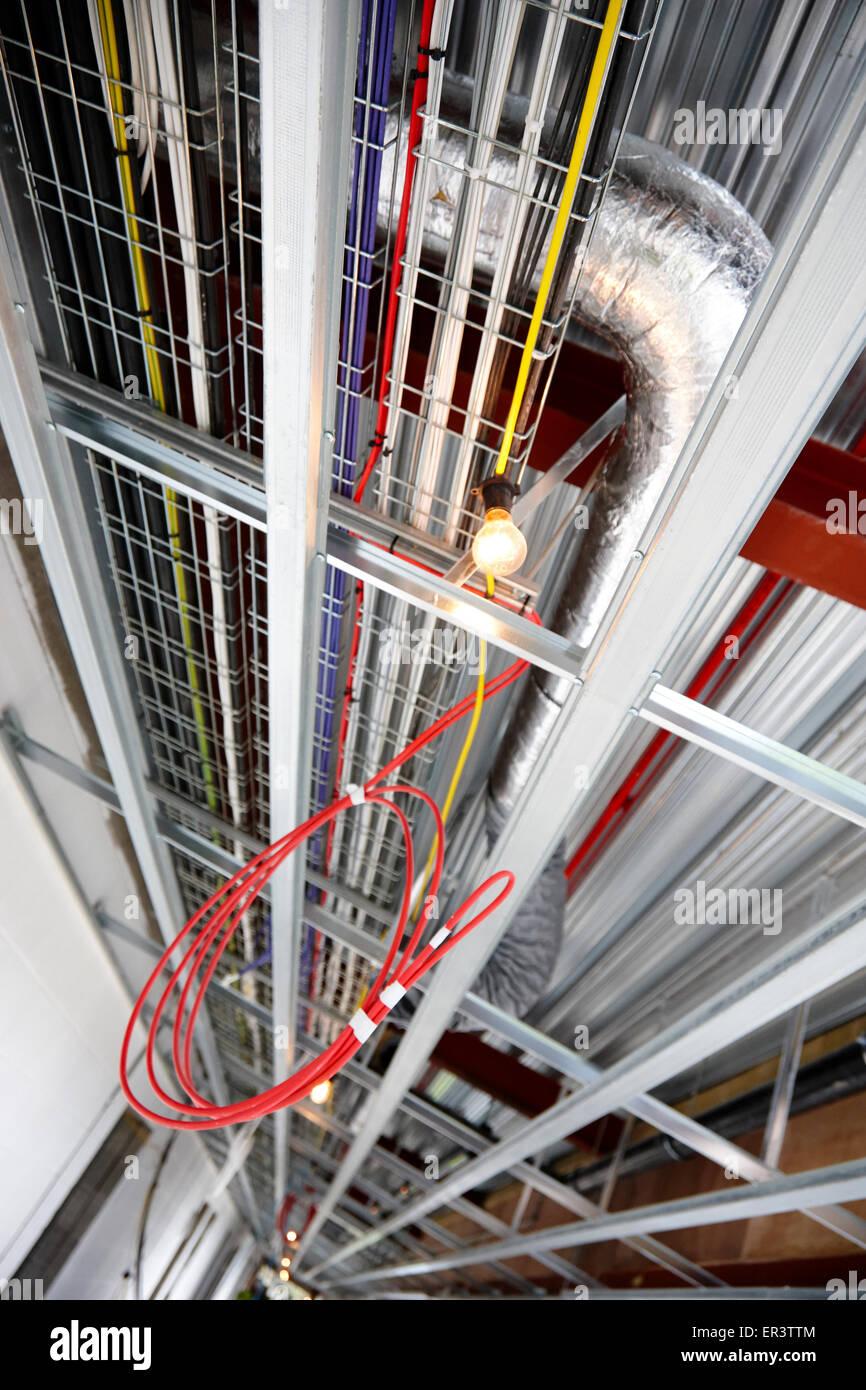 obenliegende Kanalisierung und elektrische Verkabelung in einem neuen Build-Bürogebäude in Großbritannien Stockbild