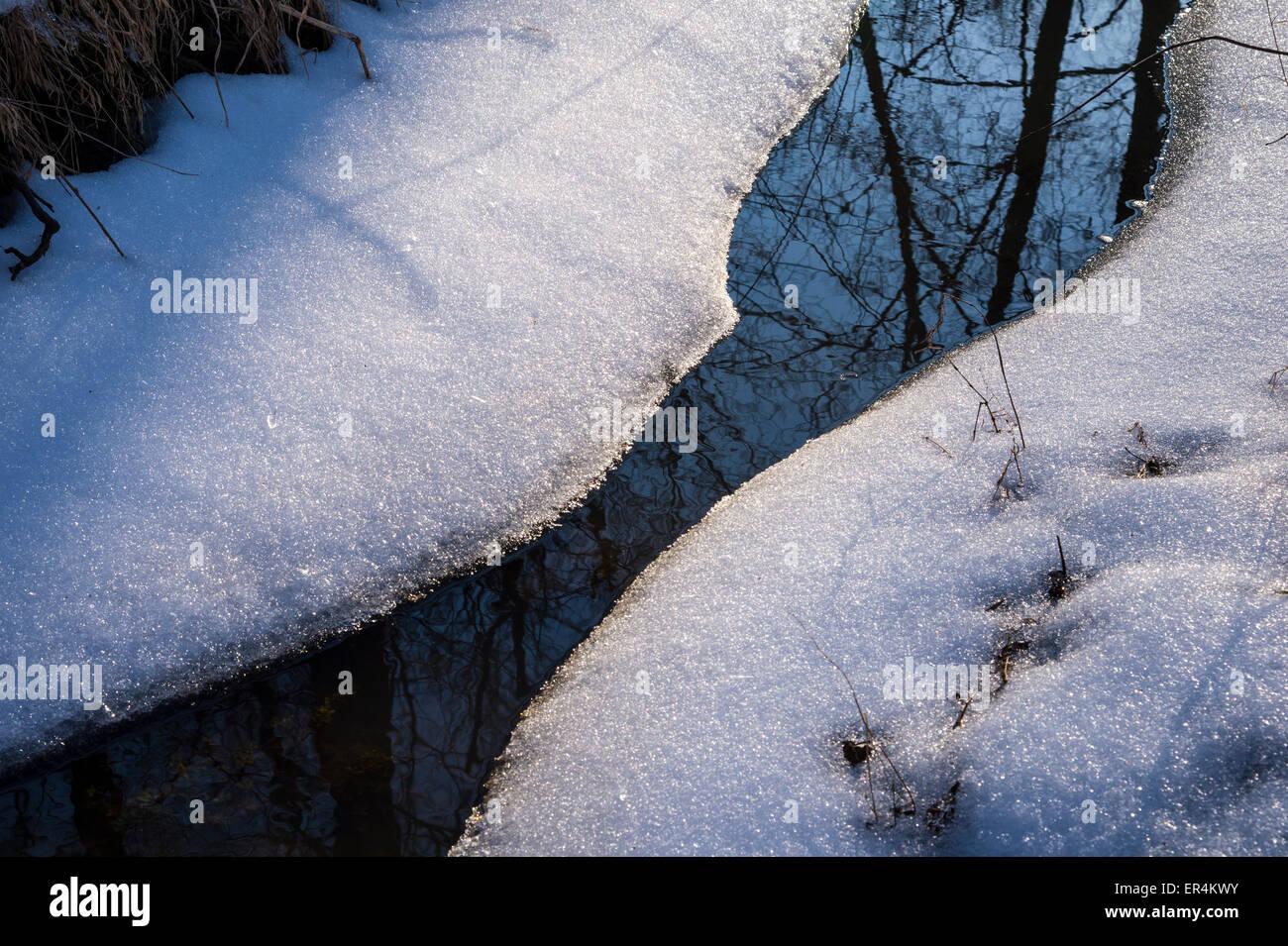 Teilweise gefrorenen Bach mit Schnee & Reflexion Stockbild