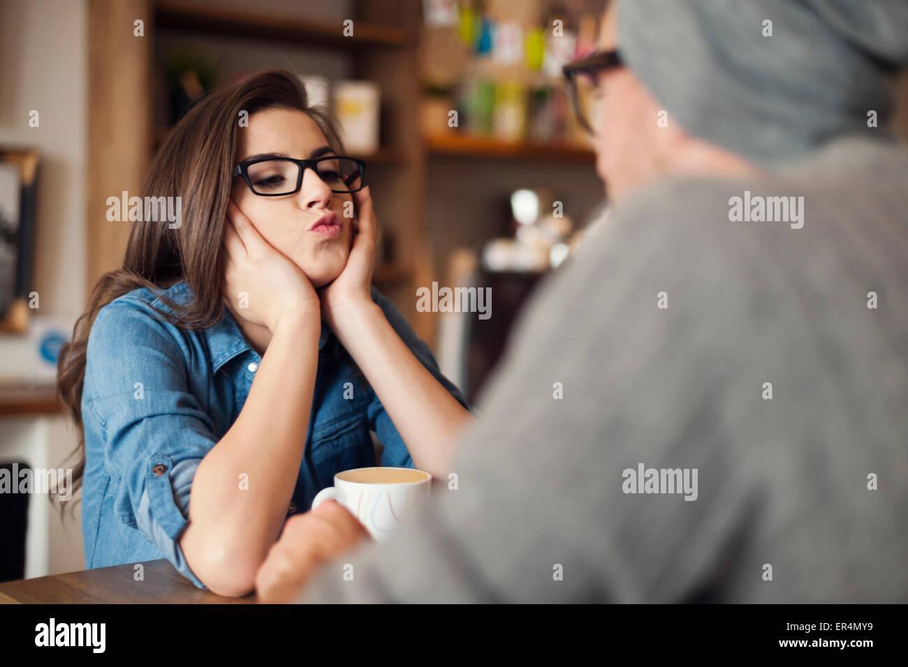 Liebende Frau bläst Küsse zu ihrem Freund im Café. Krakau, Polen Stockbild