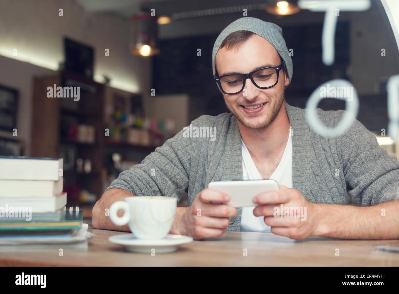 Hipster-Mann mit Handy im Café. Krakau, Polen Stockbild