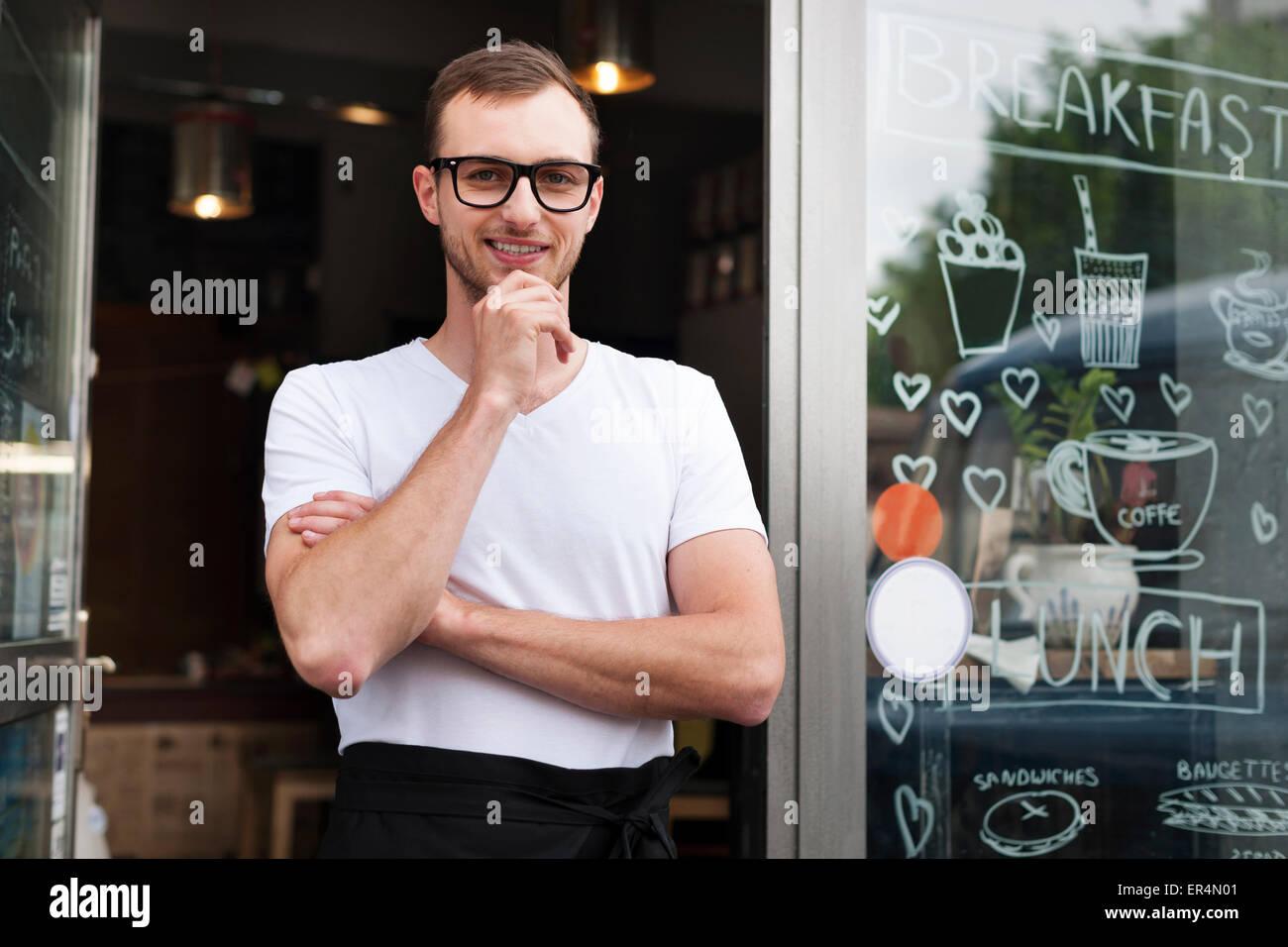 Porträt von lächelnden männlichen Kellner vor dem Café. Krakau, Polen Stockbild