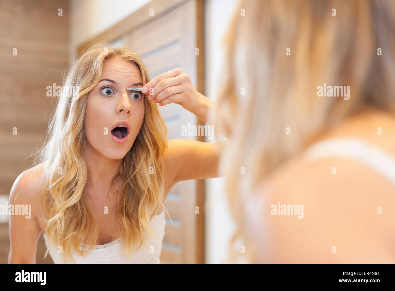 Angst, Frau tweezing Augenbrauen im Badezimmer. Debica, Polen Stockbild