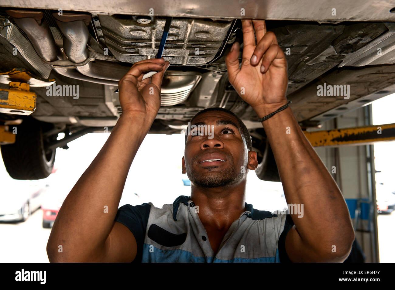 Gute Suche afroamerikanische Mechaniker Auschecken unter Beförderung des Fahrzeugs Stockbild
