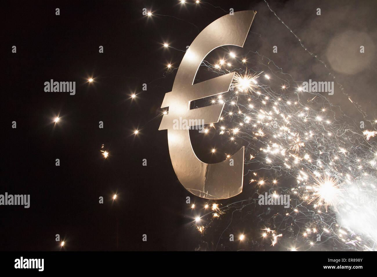 Beleuchtete Eurozeichen mit Feuerwerk in der Nacht Stockbild