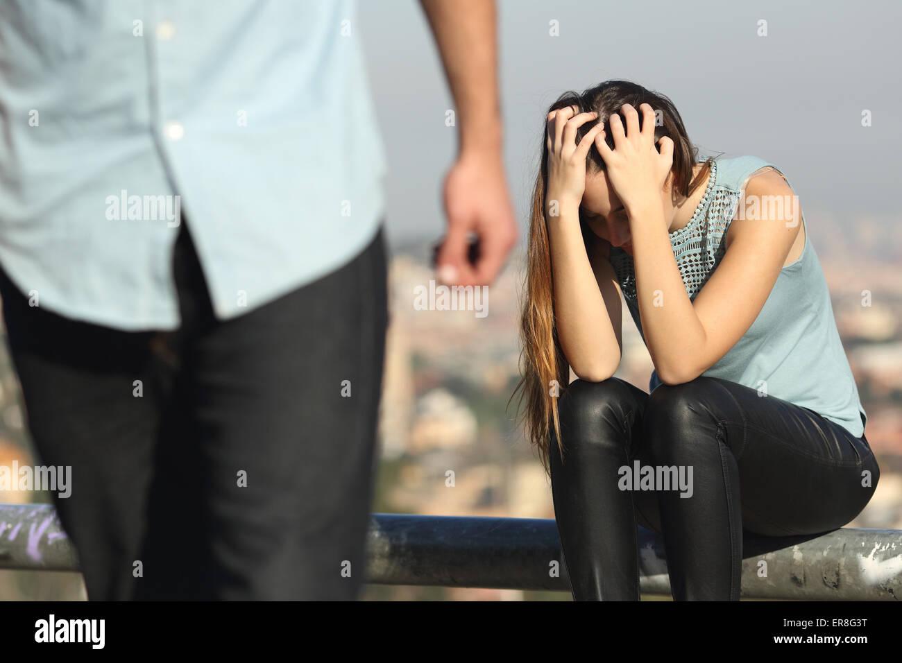 Trennung eines Paares mit Bösewicht und traurige Freundin mit einer Stadt im Hintergrund Stockbild