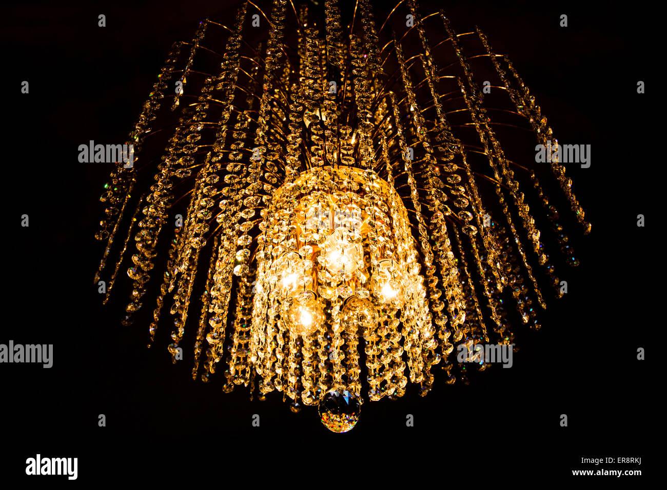Kristall-Kronleuchter leuchtet mit goldenem Licht auf dunklem Hintergrund Stockbild